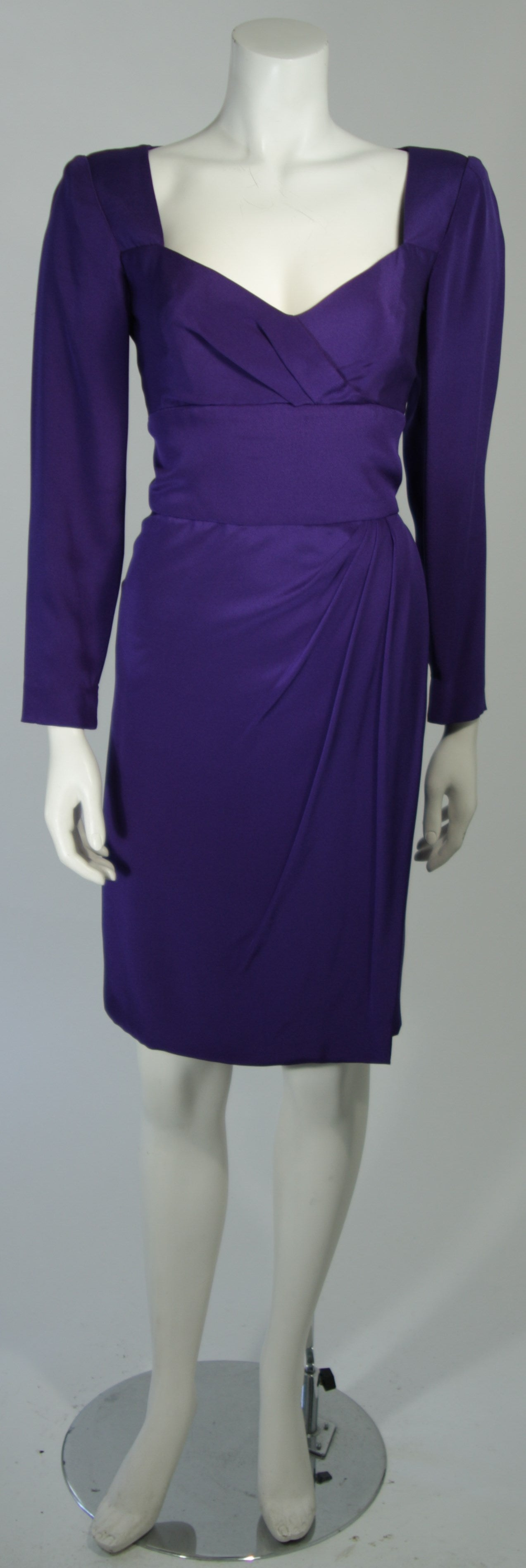 This Travilla cocktail dress is fashioned from a wonderful purple silk. The dress features a v-neckline, draping at the hip and bust, with long sleeves. There is a center back zipper. In excellent vintage condition.  **Please cross-reference