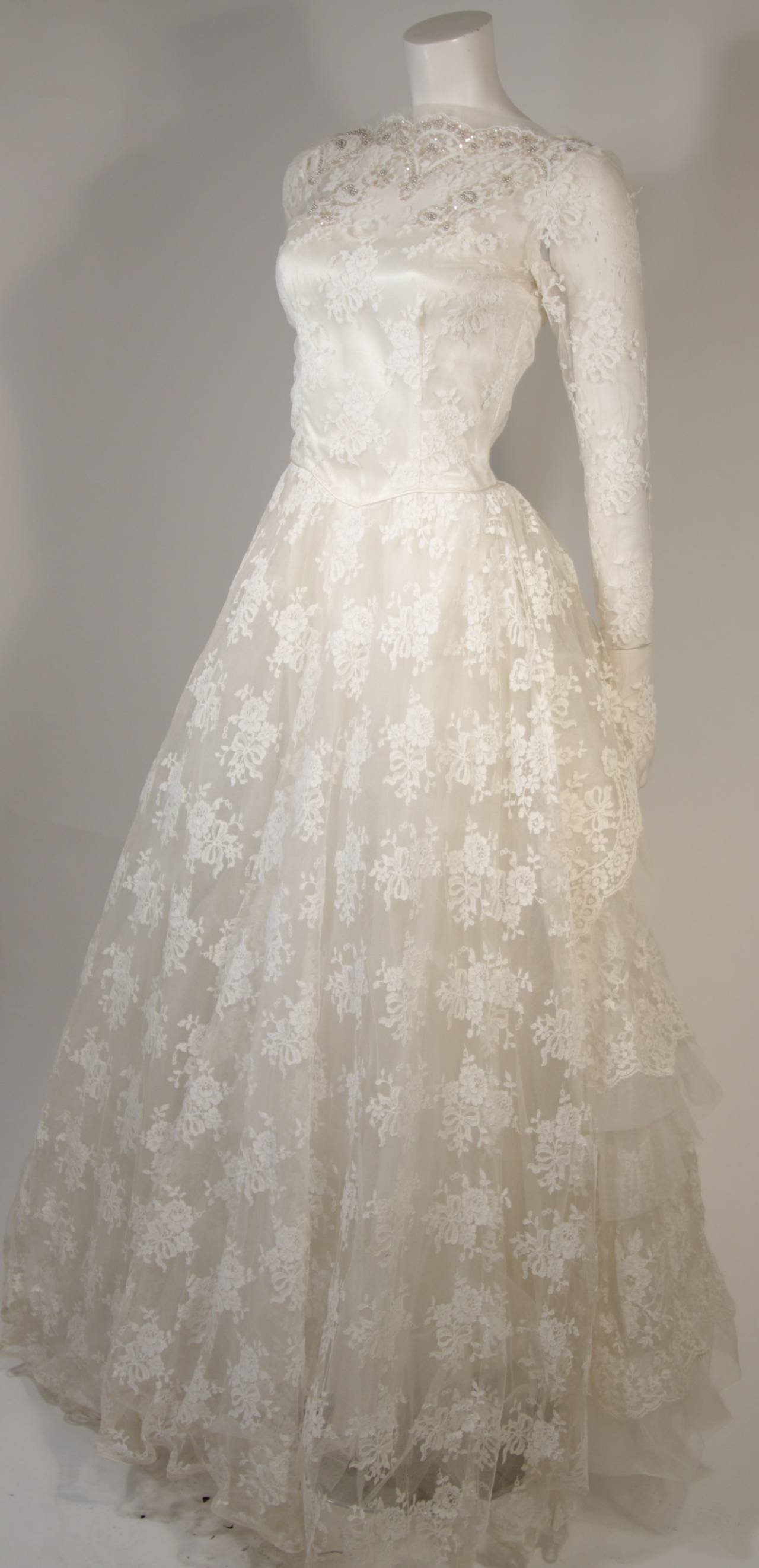 This vintage wedding gown is fabricated from layers of white lace featuring scalloped edges and satin. The scalloped neckline is adorned with sequins and pearl accents. There are center back button closures. The dress has some slight discoloration