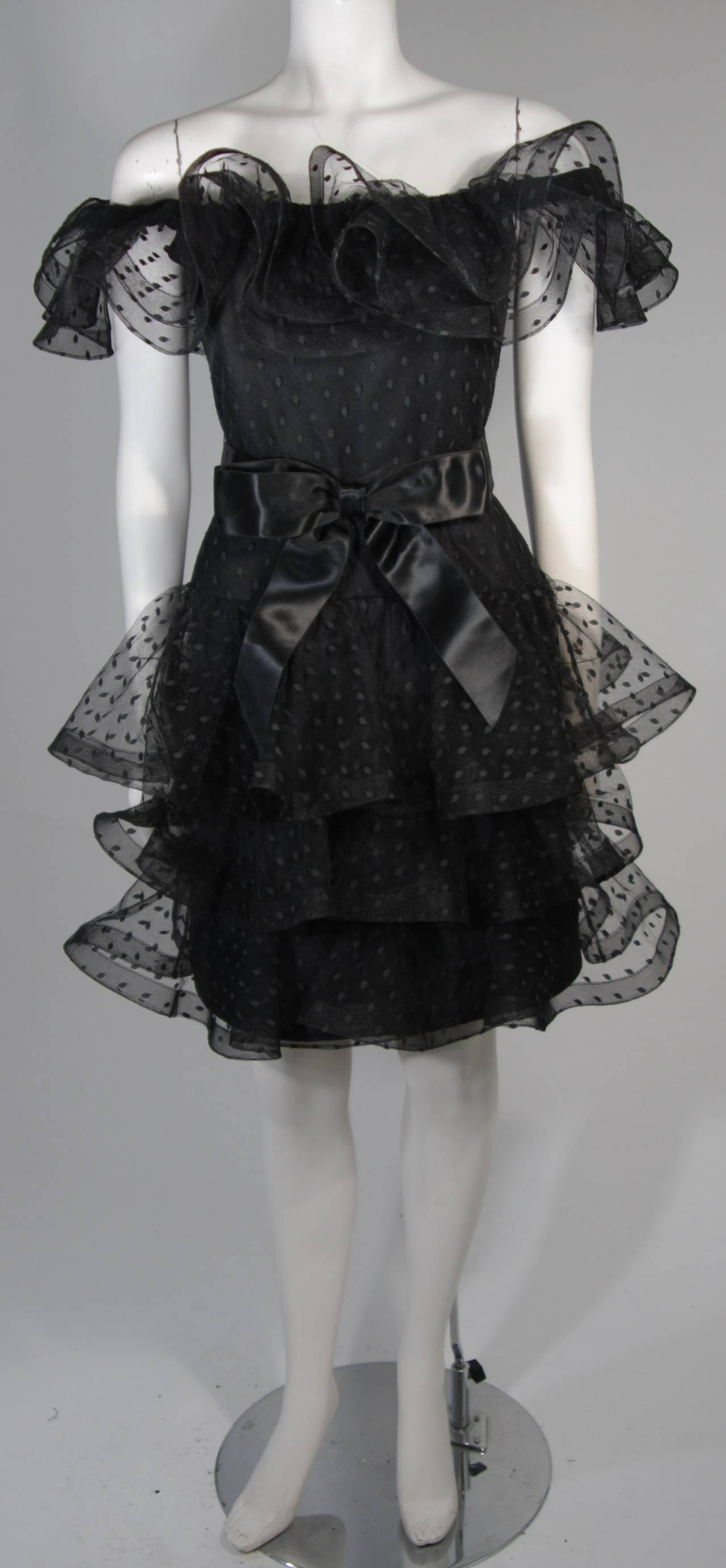 """This Victor Costa cocktail dress is fabricated from layers of black mesh fabric accented with a polka dot design. The ruffled hem lines are slightly structured due to the """"Horsehair"""" braid hemline. There is a center back zipper. In excellent"""