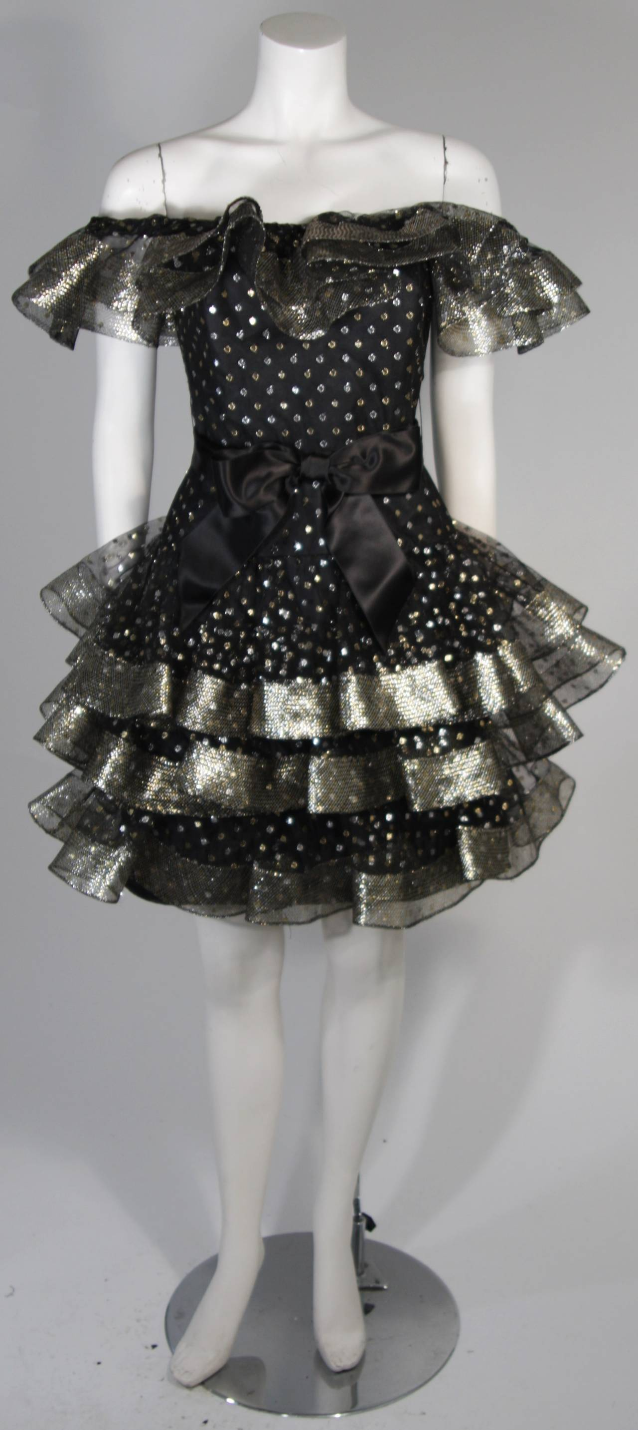 "This Victor Costa cocktail dress is fabricated from layers of black mesh fabric accented with silver and gold metallic polka dots. The ruffled hem lines are slightly structured due to the ""Horsehair"" braid hemline. There is a center back zipper. In"