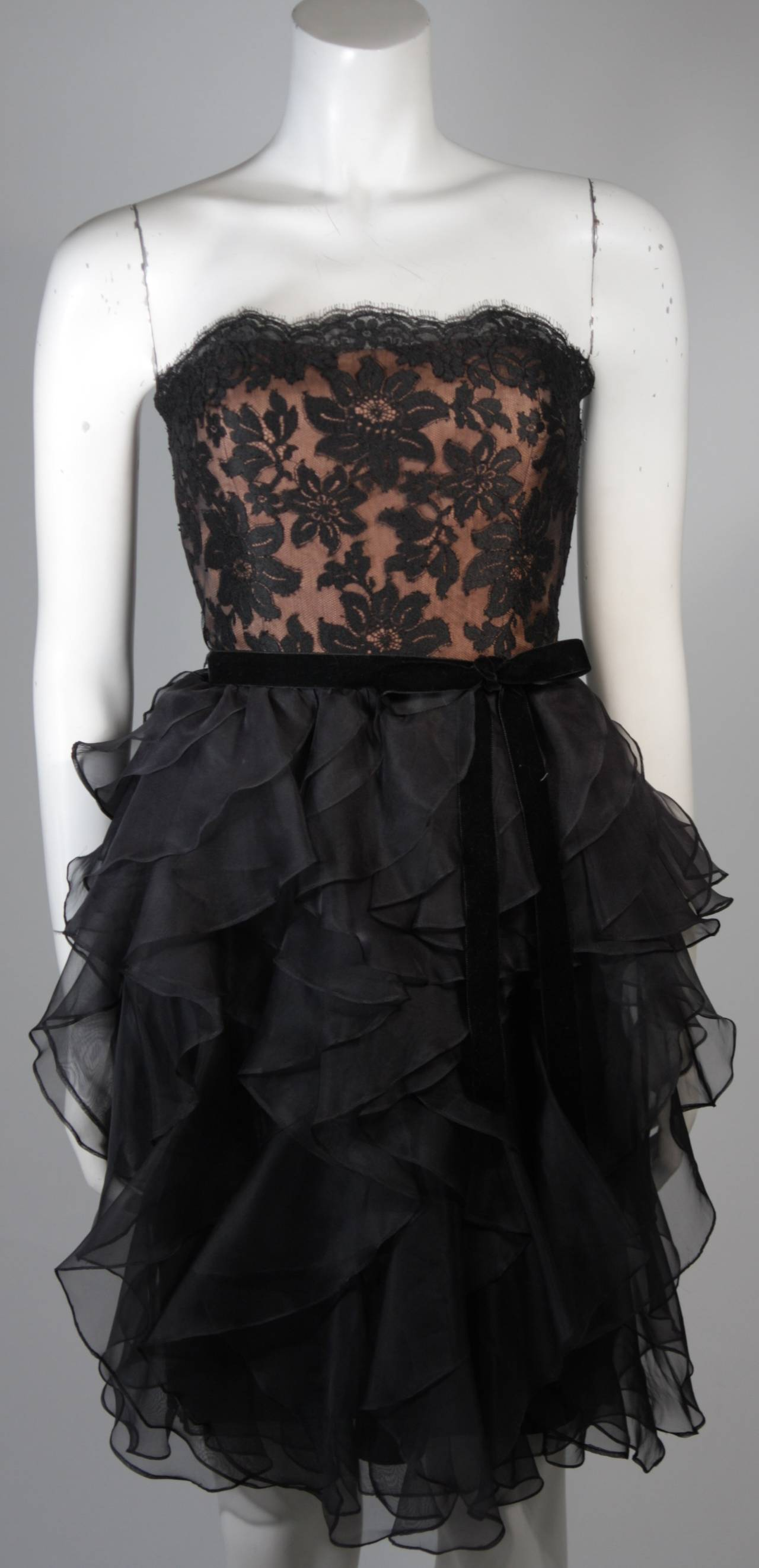 This Jill Richards cocktail dress is composed of black lace and features a lovely layered black silk skirt, comes with velvet bow. There is a center back zipper. In excellent condition.