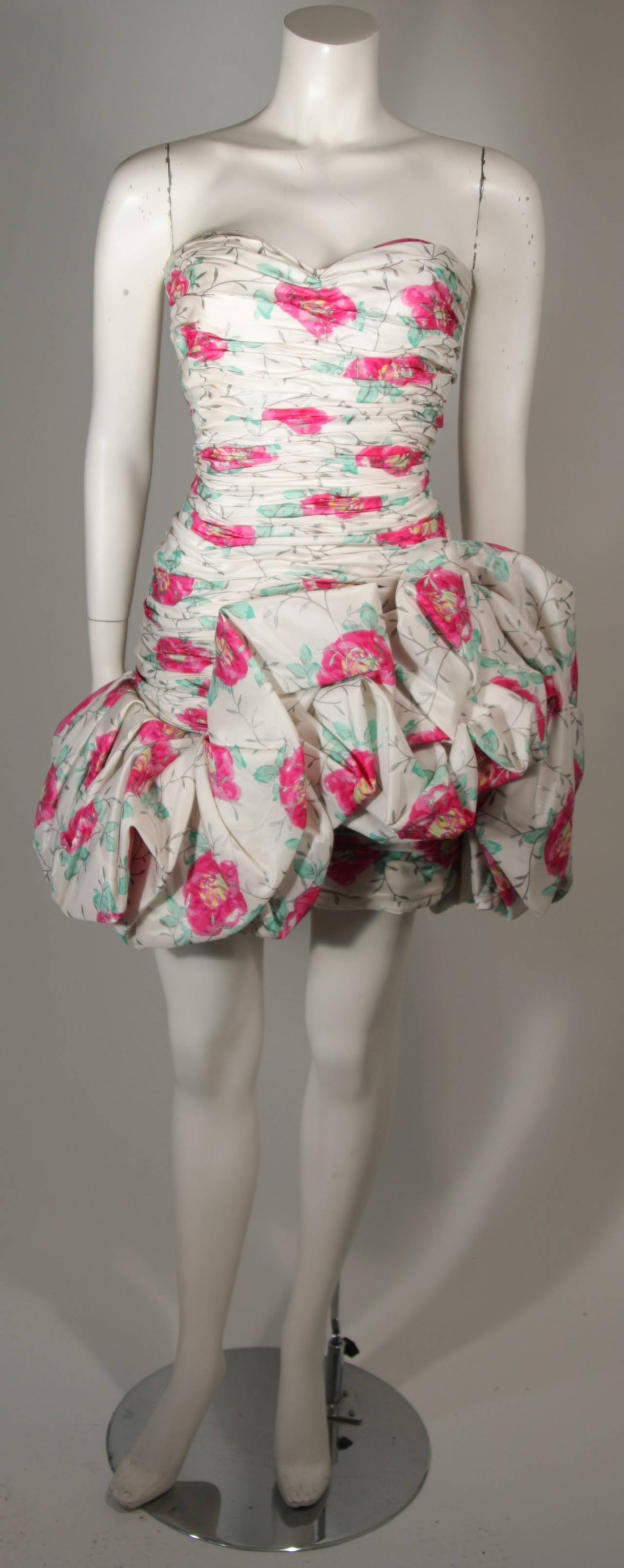 This Ungaro cocktail dress is composed of a white silk taffeta with a floral design of pink and green with silver branches. This cocktail dress features volume at the skirt and a gathered bodice with boning at the sides. There is a center back