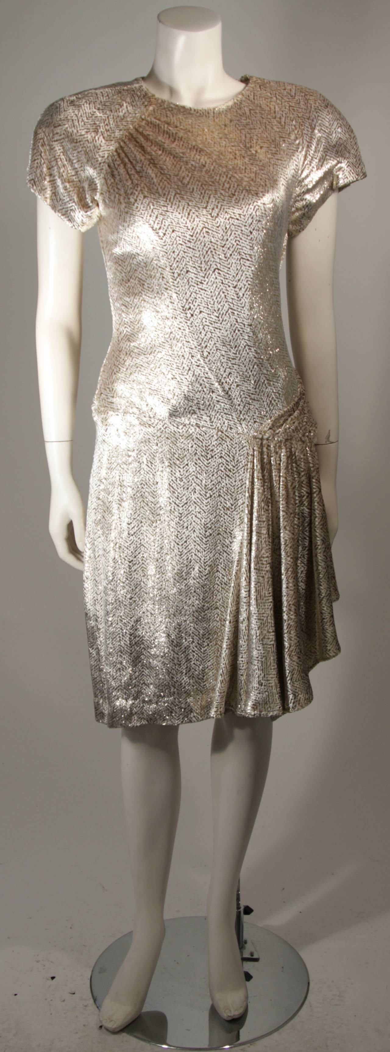 This Vicky Tiel dress is composed of an Ivory and gold metallic velvet blend. There are gathers and draping at the hip with padded shoulders, and a center back zipper closure. In excellent condition. Made in France.  This item is from the personal