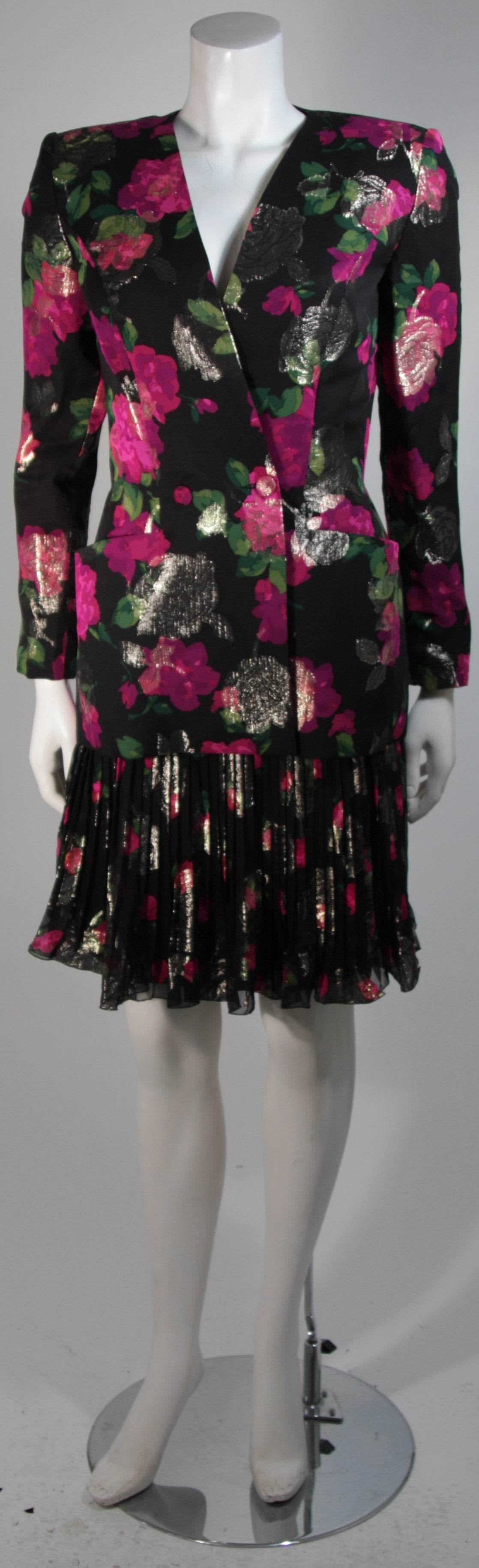 This Vicky Tiel suit is composed of a black silk with a floral motif. The jacket features a center front button fastening and pockets. The skirt is composed of a silk chiffon with pleating and zipper fastening. In excellent condition. Made in