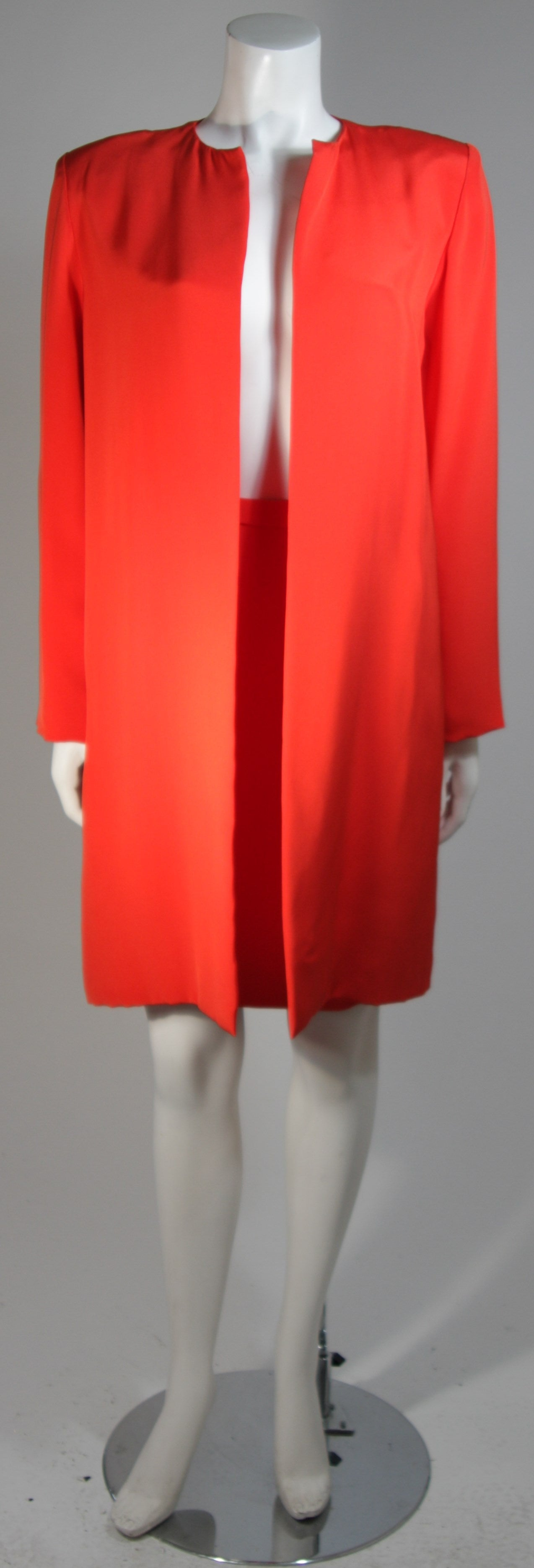 This Vicky Tiel suit is composed of an orange silk. The jacket has an open front style. The skirt is a classic pencil silhouette with a side zipper. In excellent condition. Made in France.