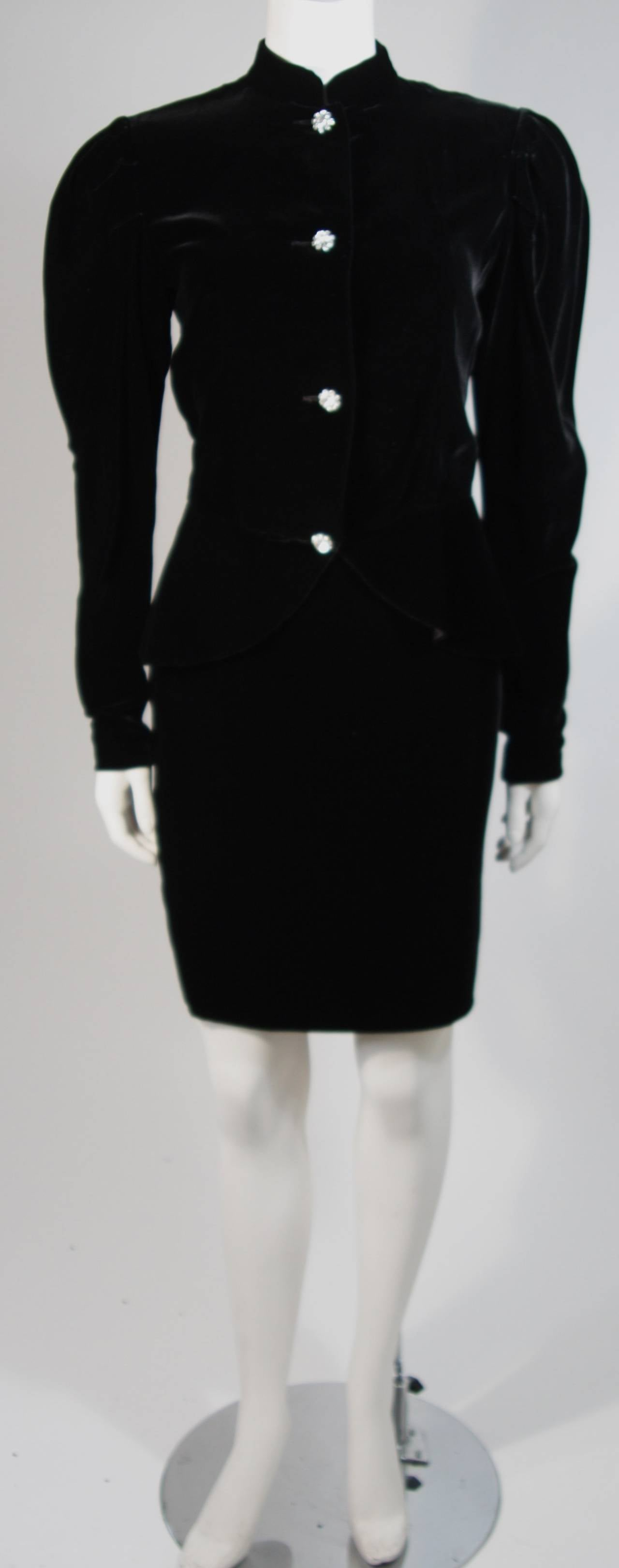 This Vicky Tiel skirt suit is composed of a black velvet and features rhinestone buttons. There are gathers at the sleeve for a dramatic effect and a peplum  style waist. The pencil style skirt has a zipper closure for ease of access. In excellent