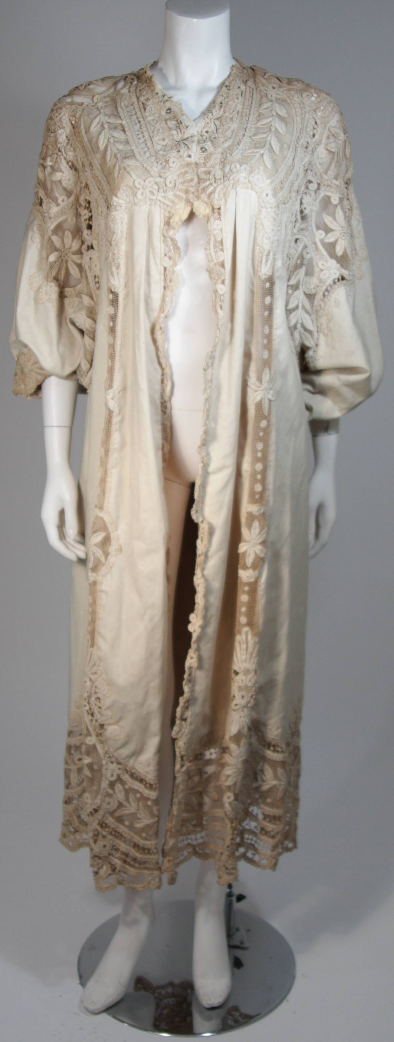 This antique coat is composed of off white natural material, with a tea stained hue, featuring bell style sleeves. There are hook and eye closures. This garment is antique and does show signs of age, should be handled with care.