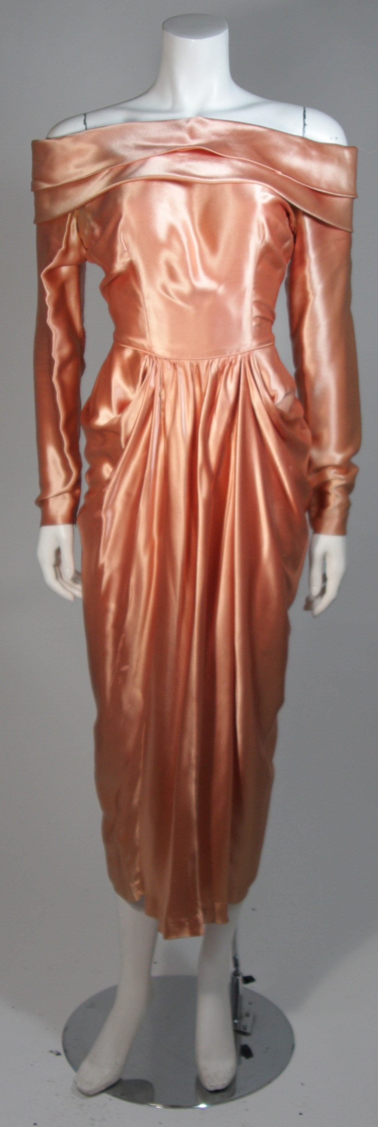 This Ceil Chapman gown is composed of peach champagne silk. The dress features a draped off the shoulder design as well draping from the waist. There are center back buttons. In good vintage condition, excellent for design purposes, the silk has