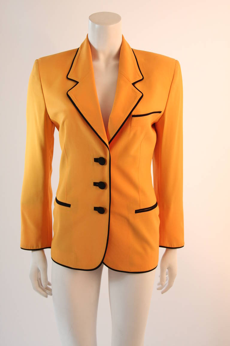 "This is a brilliant Moschino design. This blazer is in an ultra hue of yellow and features black piping and trim through out the entire jacket. The jacket has two front pockets and center front buttons. The back displays a large ""Smiley Face"". This"