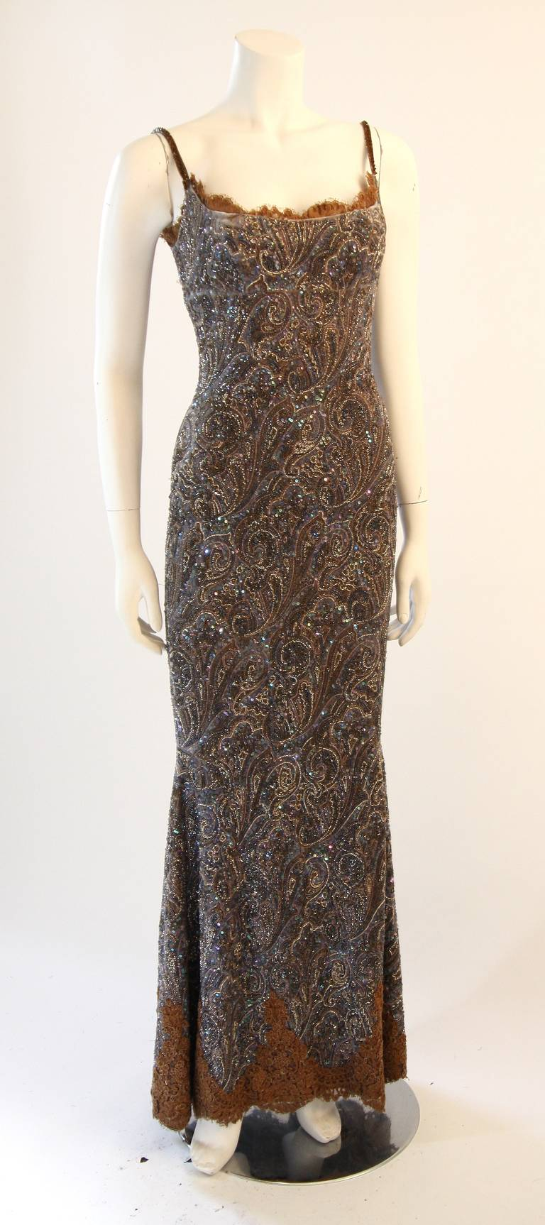 This is an exquisite Randi Rahm gown. The gown is a beautiful spaghetti strap design with brown lace trim. It is composed of a paisley print velvet embellished with beads and rhinestones. Features a side zipper for ease of access. Shown with an