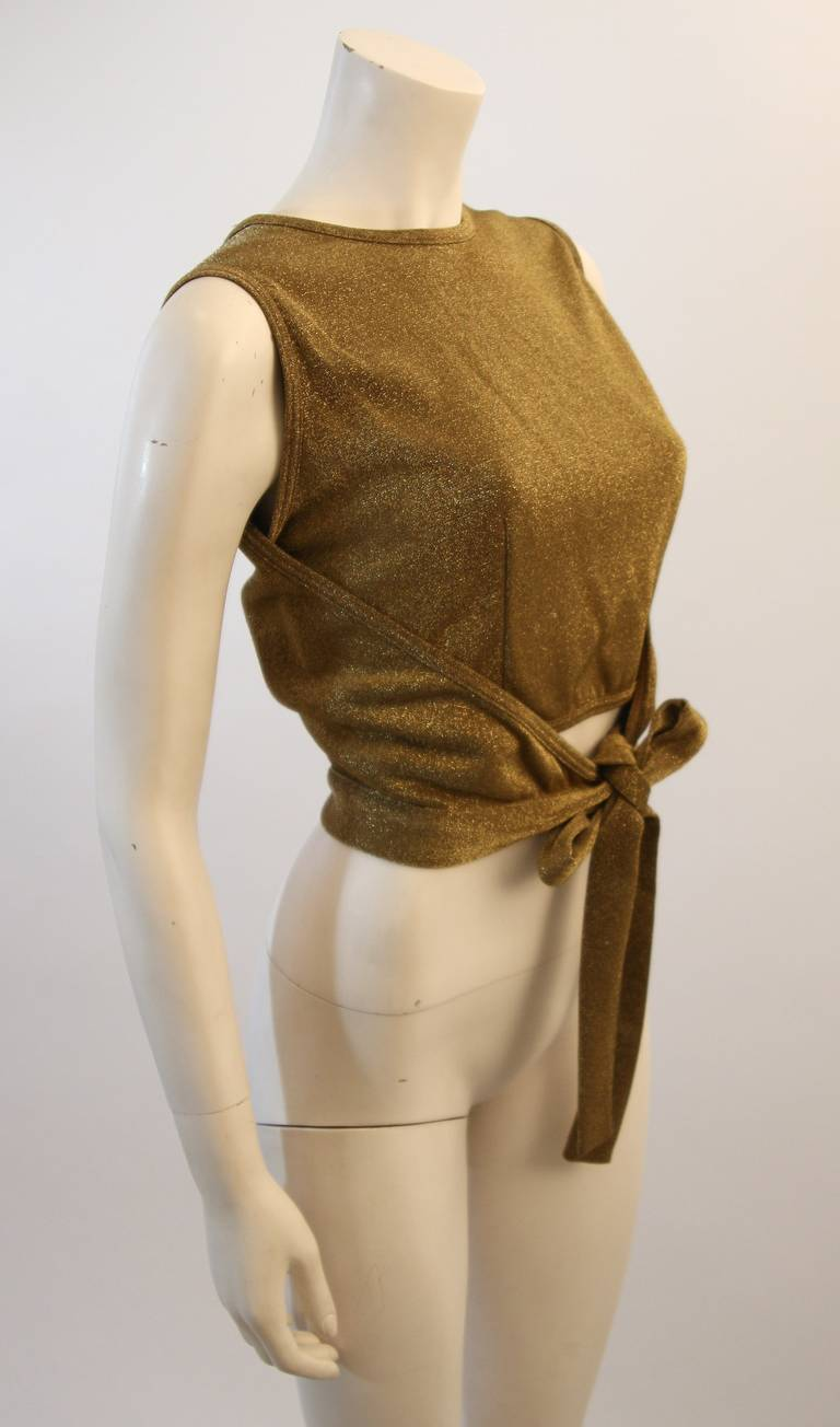This is a Moschino design. The blouse features a beautiful wrap feature and side zipper to the inner body. Composed of a gorgeous metallic fabric. Made in Italy.   Can be worn tied in front or in the back. Measures (Approximately) Size
