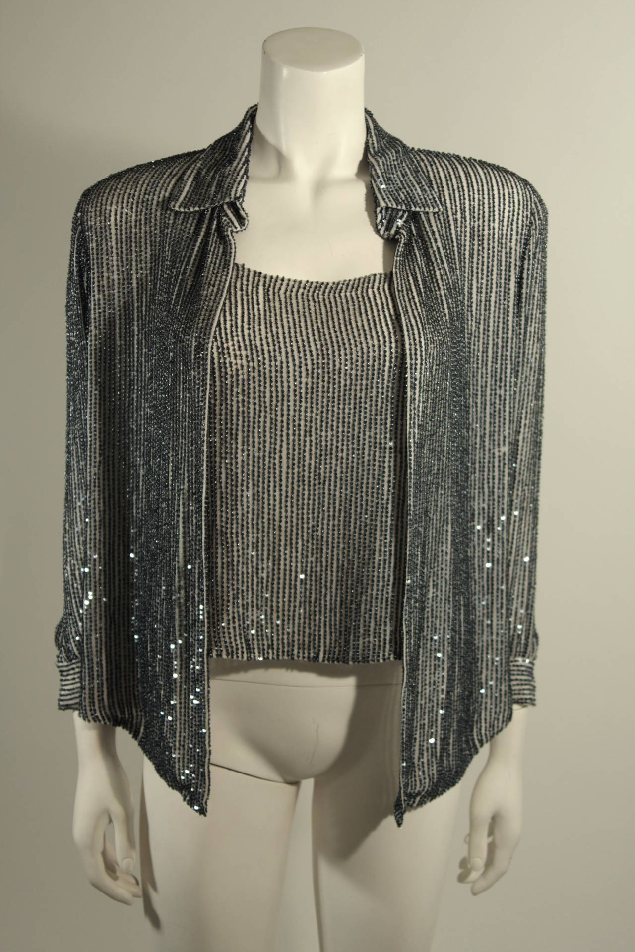 This is an Oscar De La Renta set. The evening set features two pieces; a stunning shirt and camisole combination for day or evening. The camisole has a  zipper closure for ease of access. The beads and sequins are a dark blue with