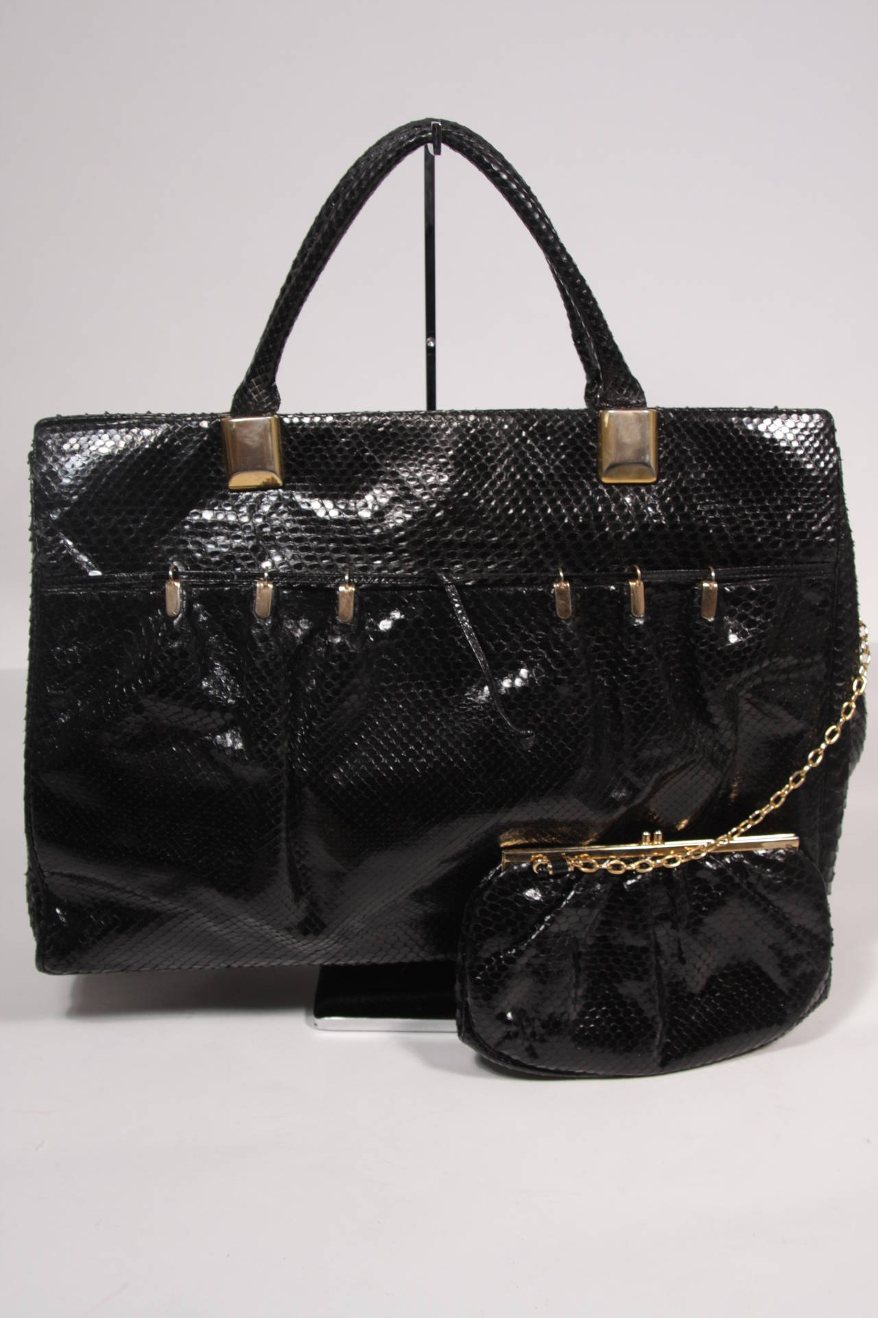 This is a gorgeous Judith Leiber purse. The handbag is composed of a striking black snakeskin and features a front pocket with gather details. There are two interior zipper compartments and snap closures. Comes with large coin purse attached by gold