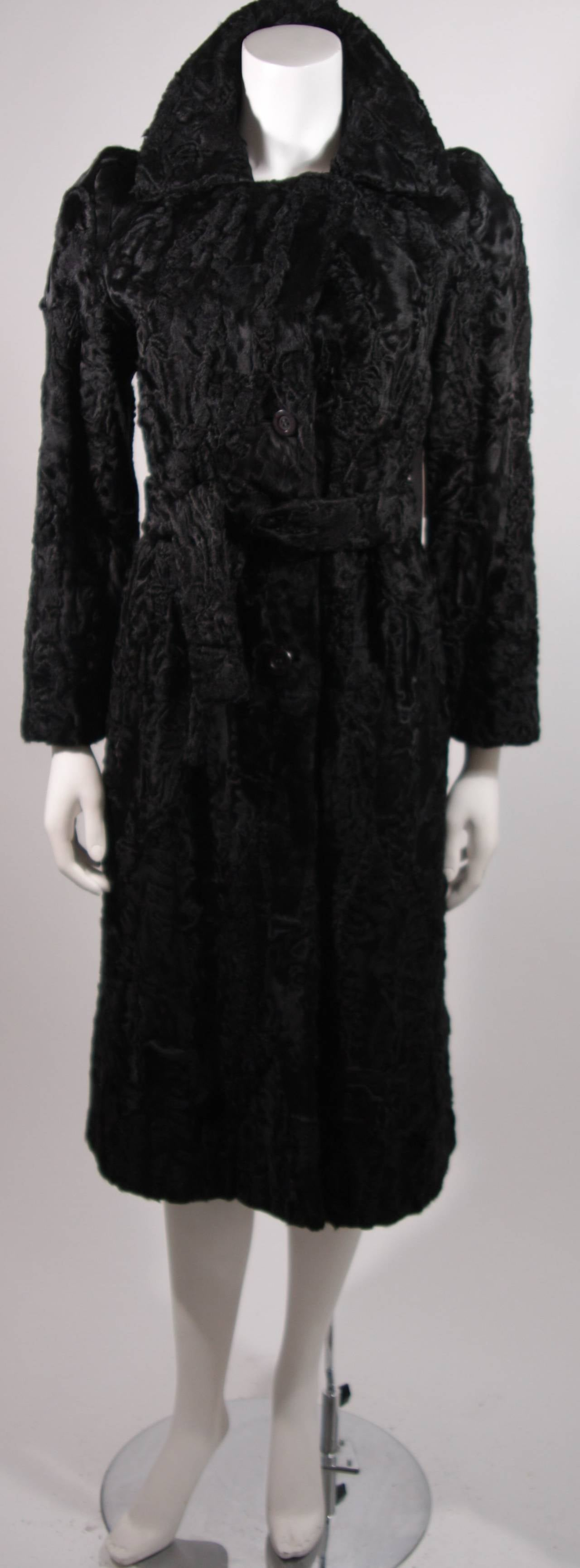 This is a stunning Donald Brooks coat. The coat is composed of a black Russian Broadtail featuring a lovely collar which may be styled up or down. There are center front buttons, two side pockets, and a wonderful waist tie belt. The back of the