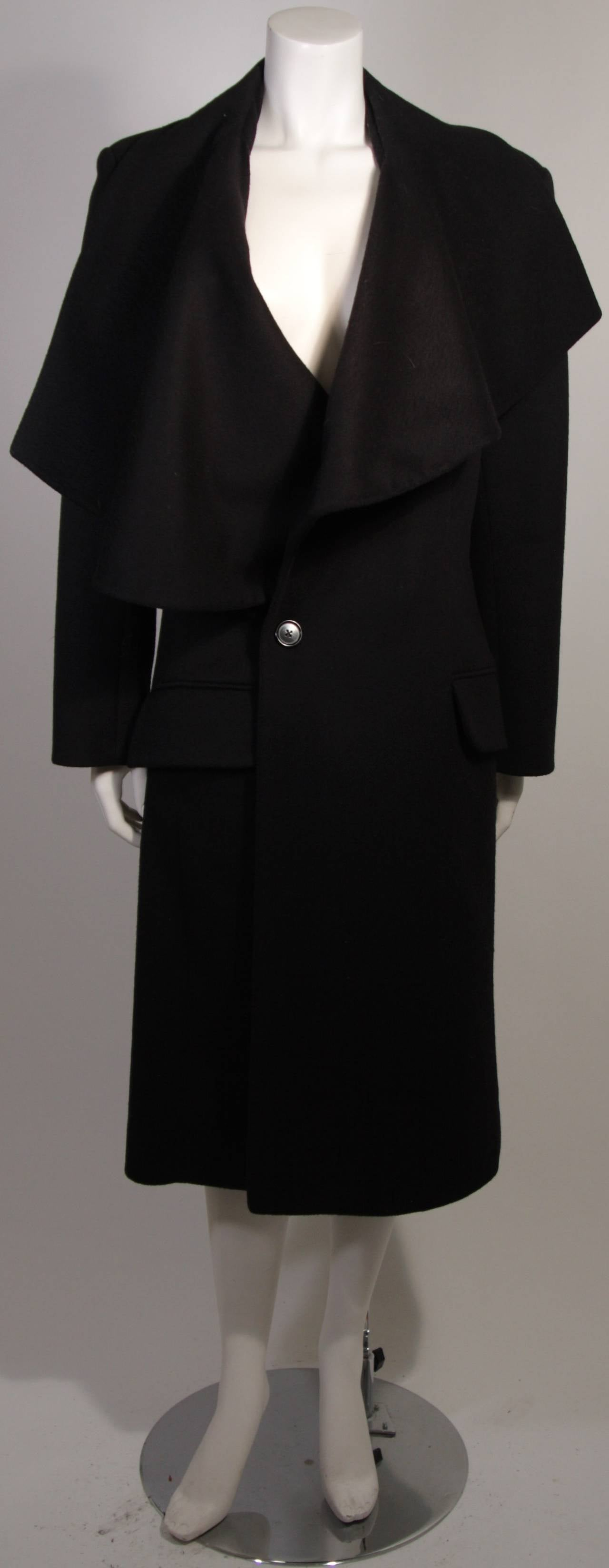 This is a John Galliano coat. The striking coat features an abstract over size collar.  90% wool and 10% nylon and the lining is 100% silk.  The front closure buttons are made of horn and we assume were originally sewn on with silk buttonhole