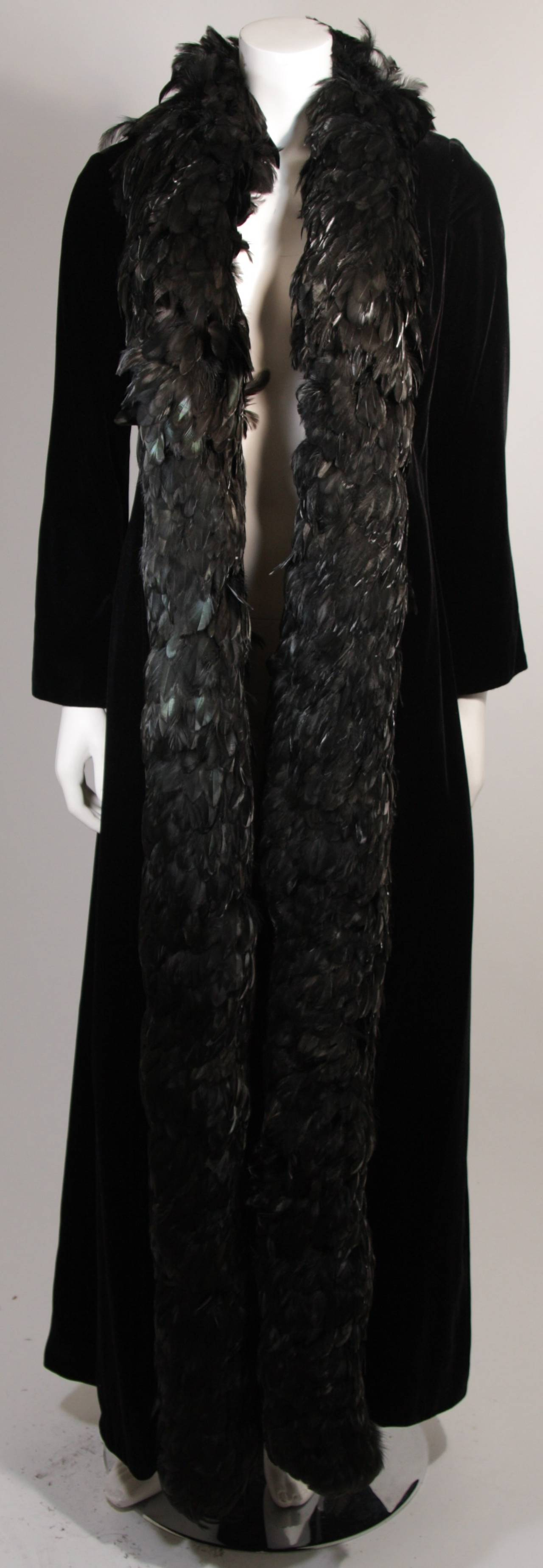 This is a striking black velvet coat trimmed with feathers designed by Victoria Royal of Hong Kong. Superb coat, shows some signs of discoloration throughout in certain lighting, lining is discolored/aged. Great design and style piece.   Measures