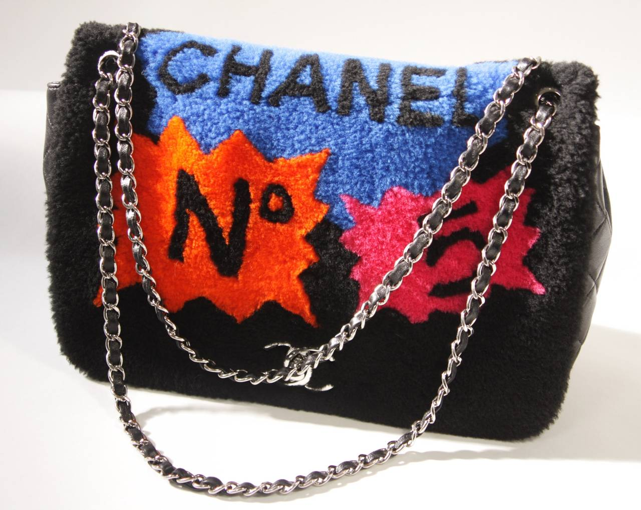 This is a Chanel design. The handbag features Chanel's classic silhouette, but is designed with a twist. The upper part of the purse is composed of a dyed black shearling with comic strip style pops of color debuting Chanel logos and branding. This