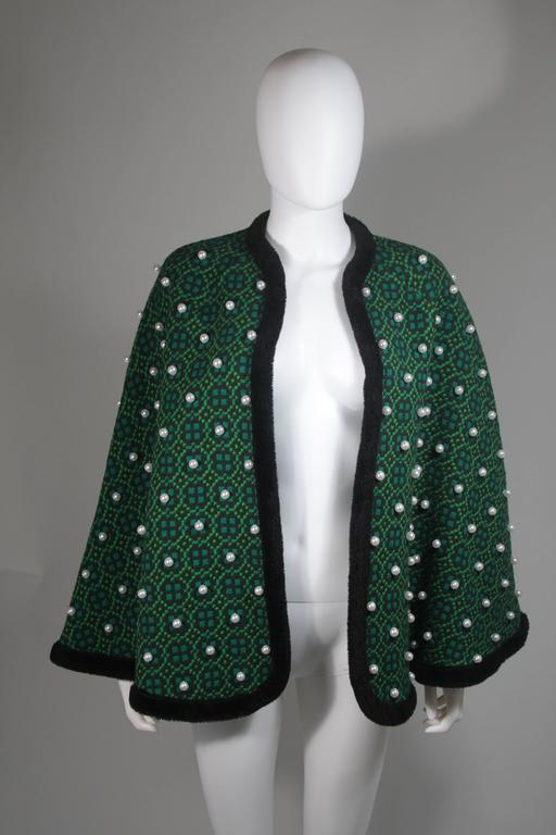 This cape is composed of a green wool with black faux fur trim. The cape is a vintage design with a modern twist, the pearl adornments are a modern addition by 'Vutique'. The cape is an open style. In excellent vintage condition.     **Please