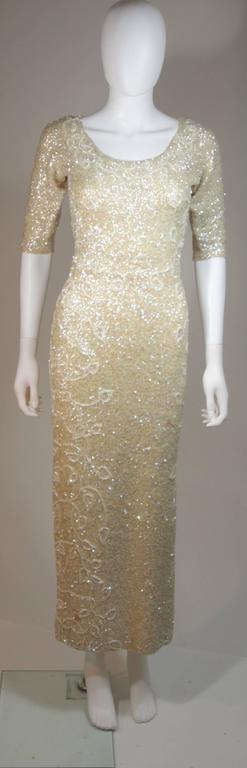 This Gene Shelley's gown is composed a stretch sequined wool knit, adorned with sequins and beading in a floral motif. There are 3/4 length sleeves and a center back zipper. In excellent vintage condition.     **Please cross-reference measurements