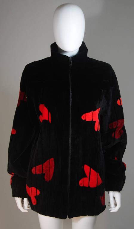 This Beautifully Canadian Zuki coat is composed of a striking color infused sheared beaver. The ultra soft coat features a black and red hearts motif. There is a center front zipper closure. There are velvet lined side pockets and a perfect collar.