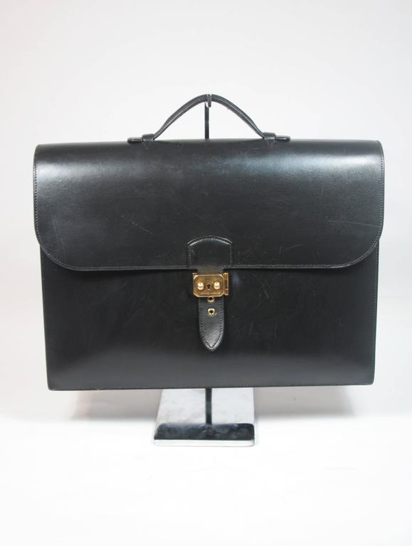 This Hermes briefcase is composed of a black box leather and features gold hardware. There is a top handle and three large interior compartments. The bag is in great vintage condition, there are some indentations at the top of the bag by the handle