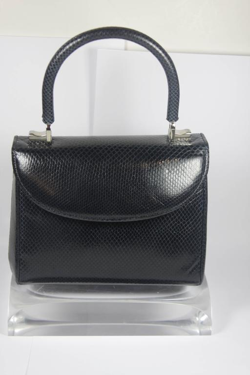 This Judith Leiber evening purse is composed of a navy lizard skin with silver hardware. There is a flap closure. In excellent condition, comes with original dustbag. 