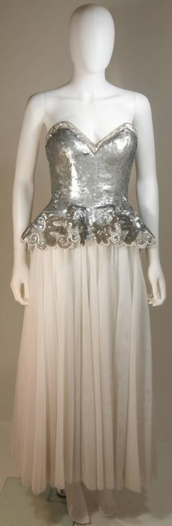 This Fabrice New York Couture  gown is composed of a silver sequined bustier with white mesh skirt. There is a zipper back closure and peplum style. In excellent condition. 