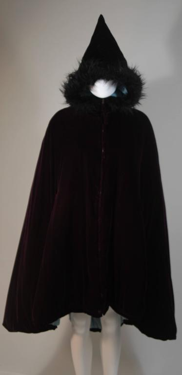 This Jean Paul Gaultier cape is composed of a purple velvet and features a baby blue lining. There is faux fur trim at the pointed hood. Features a center front zip closure. A very interesting design. In excellent condition, the baby blue lining has
