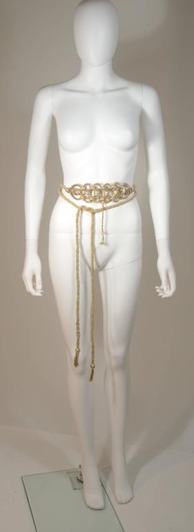 This Oscar De La Renta belt is composed of a braided gold metallic material and features a tassel style. In excellent condition. 