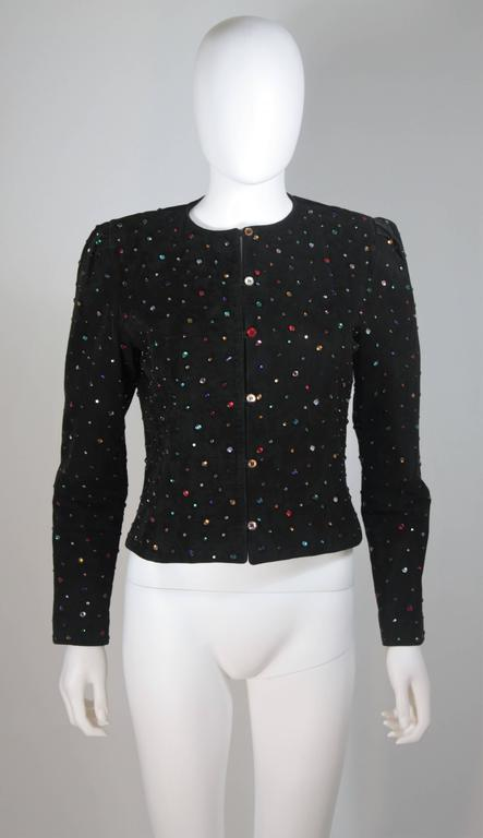 This jacket is composed of a black suede and features multi-color rhinestone applique. There are center front button closures. The shoulders features a gathered detail. In great vintage condition. 