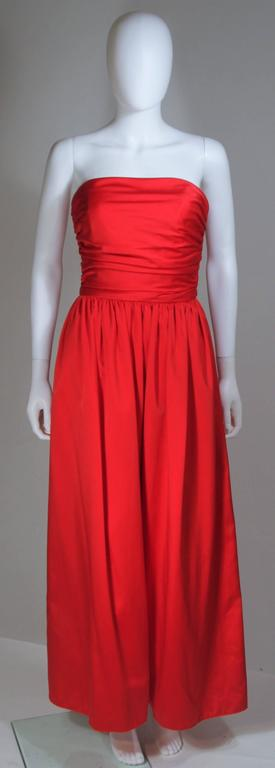 This Anthony Muto gown is composed of a red silk with gathered bodice and full skirt. Features a tie at the waist and center back zipper. In excellent vintage condition.   **Please cross-reference measurements for personal accuracy. Size in
