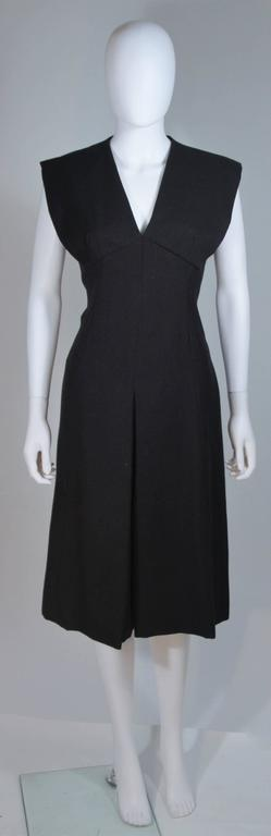 This Mollie Parnis cocktail dress is composed of a black linen. Features an A-Line silhouette, with large center front pleat, and center back zipper. In excellent vintage condition. 