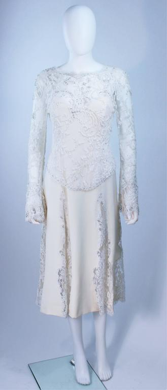 This Fe Zandi  dress is composed of a white silk and lace combination. The lace features rhinestone and bead applique. There is a center back zipper closure. In excellent vintage condition.     **Please cross-reference measurements for personal
