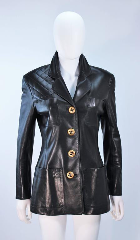 This Chanel  jacket is composed of black leather and features a quilted shoulder detail. There are center front button closures in gold with 'CC' logo detailing, as well as front pockets. In excellent vintage condition. 
