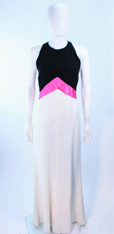 This Elizabeth Arden gown is composed of a black, pink, and cream combination with a satin contrast bow. Features a bias cut skirt. There is a center back zipper closure. In excellent vintage condition.  **Please cross-reference measurements for