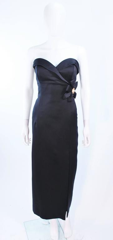 This Victor Costa gown is composed of black satin and features a side bow. There is a draped style boned bustier with front slit. There is a center back zipper closure. In excellent vintage condition.
