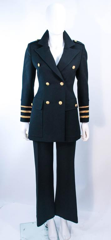 This Geinter Project pant suit is composed of black wool and features gold patch appliques. The jacket has center front button closures and the wide fit slacks have front gold button closures as well. In excellent vintage condition.  **Please