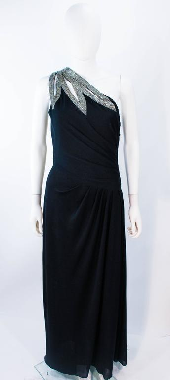 This Travilla gown is composed of a black jersey and features a stunning one shoulder style with beaded applique.  There is a draped design with rouched waist details. There is a zipper closure. Made in USA.   **Please cross-reference measurements