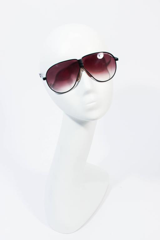 These Porsche Carrera sunglasses are composed of a black metal and have  a suede case. Features a fantastic folding style, which can easily be stored in a pocket, purse etc. In great vintage condition, lenses can be easily replaced, they show signs
