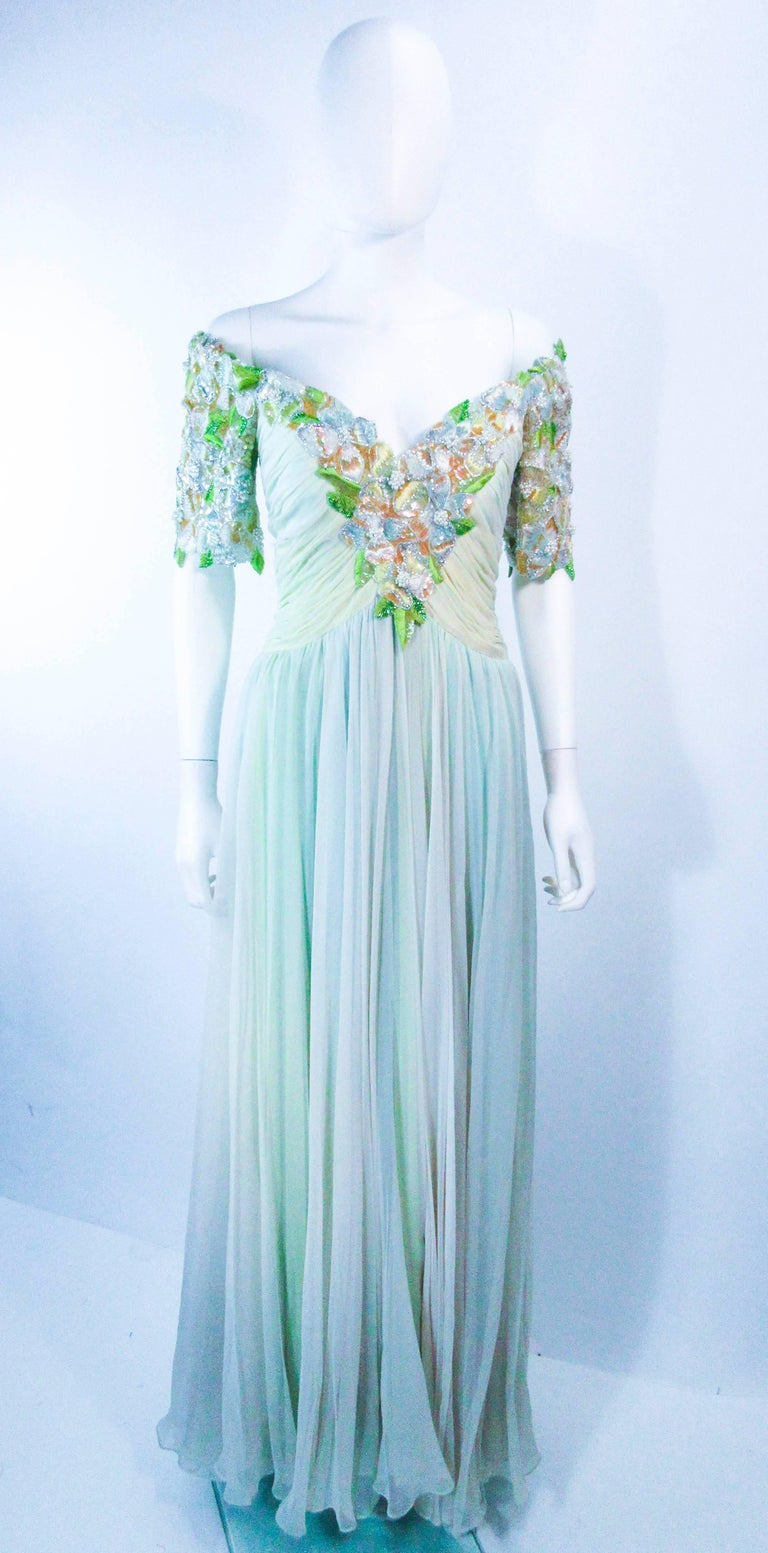 This vintage Bob Mackie gown is composed of a light green mint hue silk chiffon. The upper bodice features an embellished center front and short sleeve, with a floral pattern. There is a zipper closure with structured interior. In