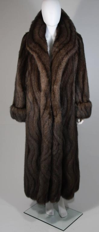 This custom Russian Sable coat is made of finest Russian Sable. This ultra supple coat features a large collar with beautifully patterned pelts that flow in a waved design. There are center front hook and closures, and side pockets. In excellent
