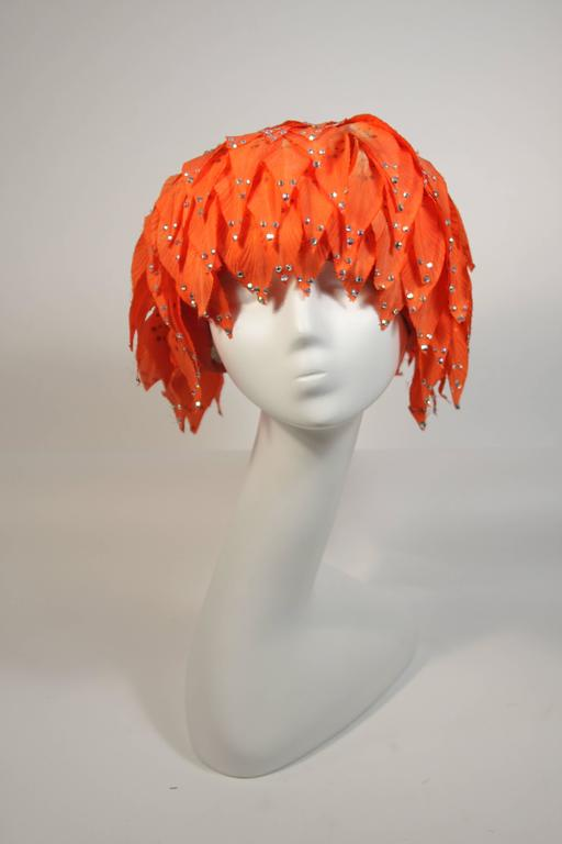 This Jack McConnell hat is composed of orange petals a-top a mesh base. The petals are adorned with rhinestones. The hat is in good condition for design inspiration and as a collectors item, there are missing rhinestones and discoloration (see