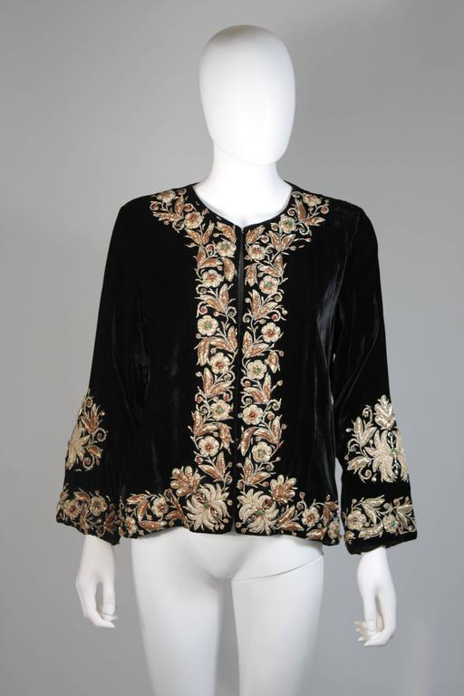 This vintage jacket is composed of a black embroidered velvet. There are center front closures. In excellent condition. 