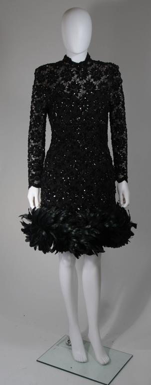 This Travilla cocktail dress is composed of an embellished lace, adorned with sequins and beading. There is a center back zipper. In excellent condition. Made in USA.