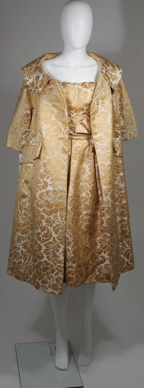This Samuel Winston evening ensemble is composed of a gold and cream brocade. The dress features a draped style at the waist which culminates to a bow. There is a zipper closure. The large opera coat features a button closure with hook and eye. In