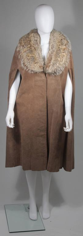This Nolan Miller cape is composed of a brown suede and features a fox fur collar. There are center front button closures. In excellent condition, lining has slight color variations due to age .  