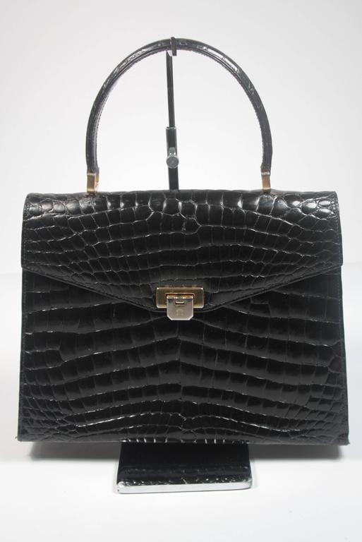 This Amir Italy handbag is composed of black Crocodile. It features multiple interior compartments and a back slot pocket. In excellent vintage condition. Made in Italy. 