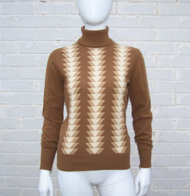 Jaeger has been making classic clothing since the turn of the 20th century.  This turtleneck sweater in light brown with a graphic arrowhead print in lighter brown and creme colors is made from high quality lambswool.  Vintage Jaeger clothing often