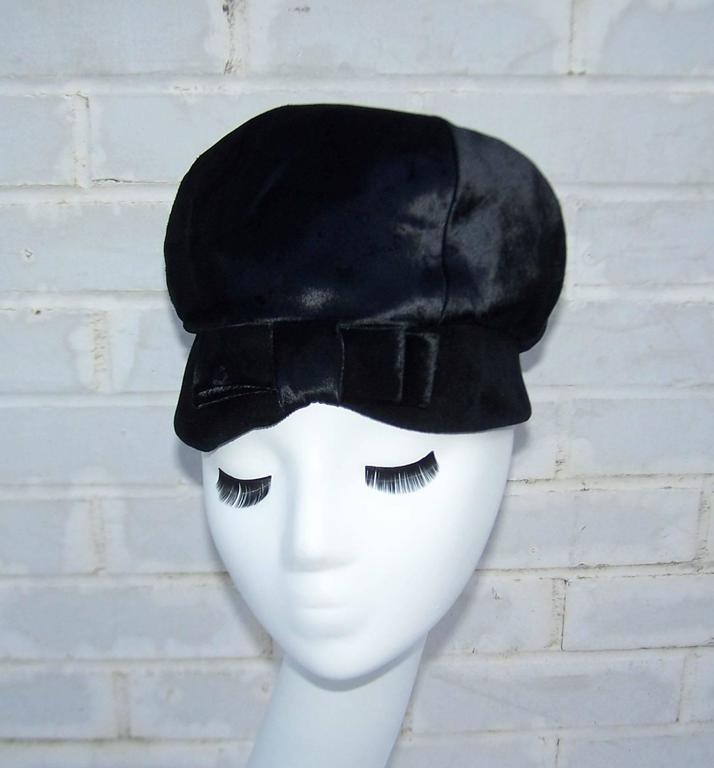 This adorable hat designed by John Harberger for his millinery line, Mr. John Jr., has a 1960's period perfect mod aesthetic.  The body of the hat is a flat velvet that has the feel and appearance of pony hide.  The face framing brim is a soft