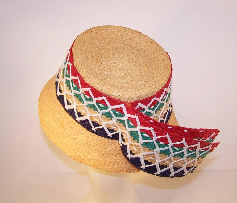 This 1950's Italian straw hat is begging for a trip to the beach!  The colorful stylized bucket hat is a natural woven grass with a striped lattice rim bedecked in red, green, navy blue and white.  The addition of tails gives the illusion of a